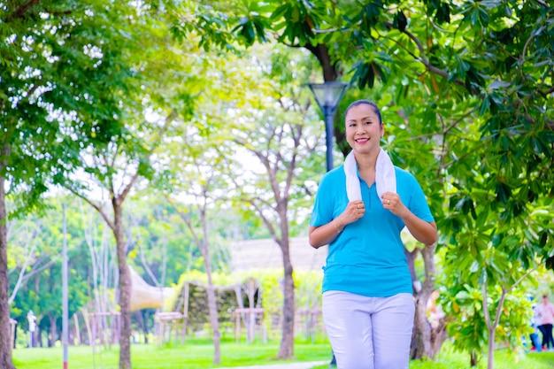 Retrato de jovem mulher asiática. ela está correndo no parque. ela é sorrir e ser feliz em boa hora