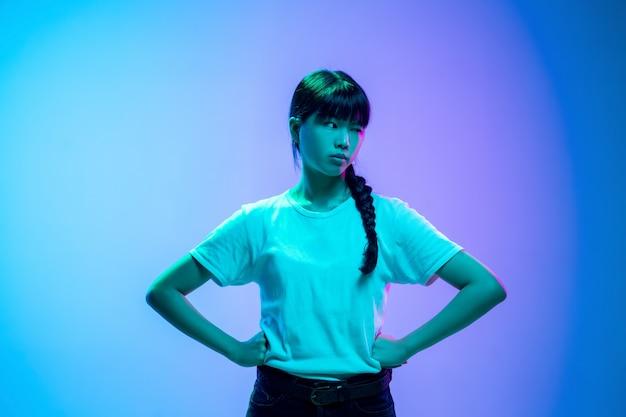 Retrato de jovem mulher asiática em fundo gradiente de estúdio azul-roxo em luz de néon