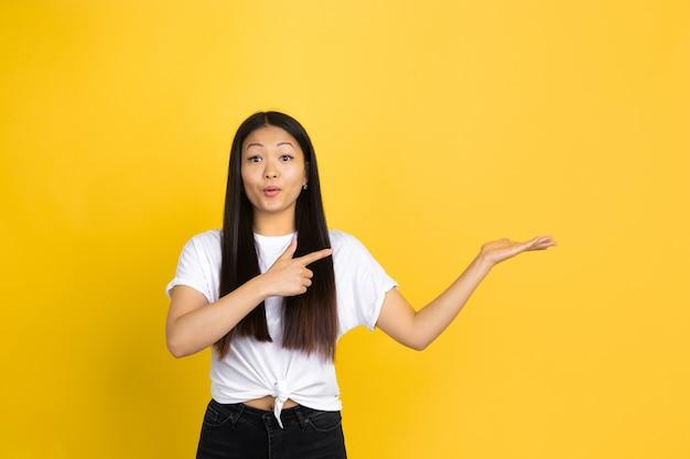 Retrato de jovem mulher asiática isolado na parede amarela