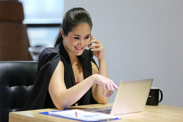 Retrato, de, jovem mulher asiática, sorrindo, olha, em, laptop