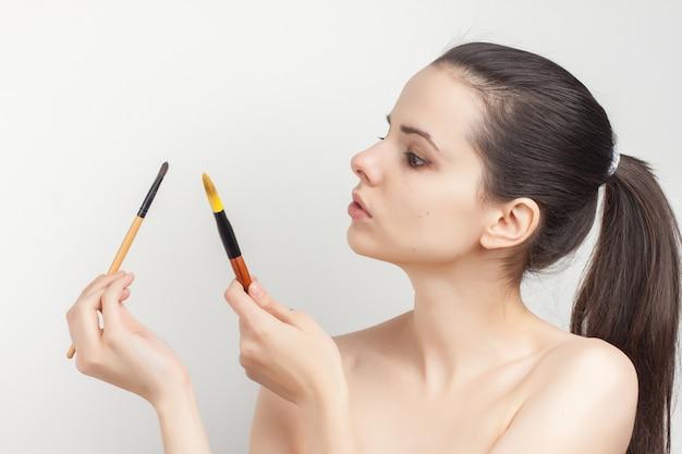 Retrato de jovem mulher bonita fazendo pincel de maquiagem