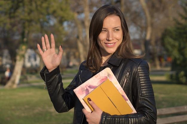 Retrato de jovem mulher branca, vestindo uma jaqueta de couro, segurando cadernos, sorrindo e acenando