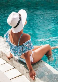 Retrato de jovem mulher bronzeada em trajes de banho azul. menina relaxante na borda da piscina no spa resort. modelo sentado no chapéu branco