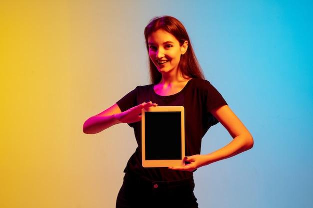 Retrato de jovem mulher caucasiana em fundo de estúdio gradiente azul-amarelo em luz de néon