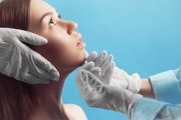 Retrato de jovem mulher caucasiana, recebendo injeção plástica