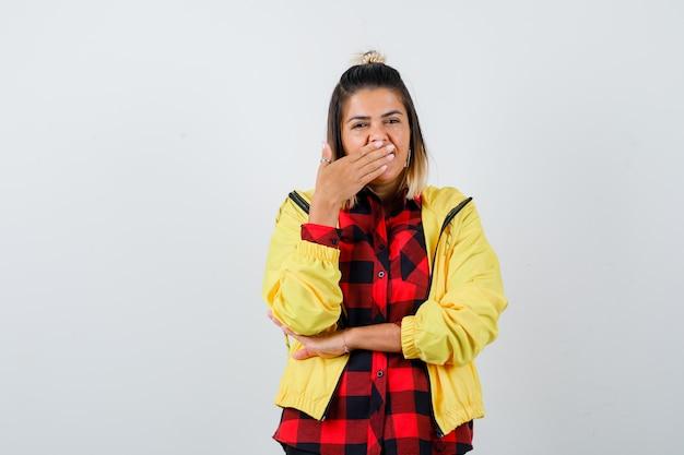 Retrato de jovem mulher cobrindo a boca com a mão em uma camisa quadriculada, jaqueta e vista frontal cansada