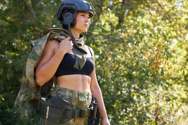 Retrato de jovem mulher com arma em traje militar ao ar livre