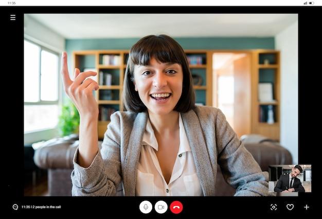 Retrato de jovem mulher de negócios em videochamada de casa