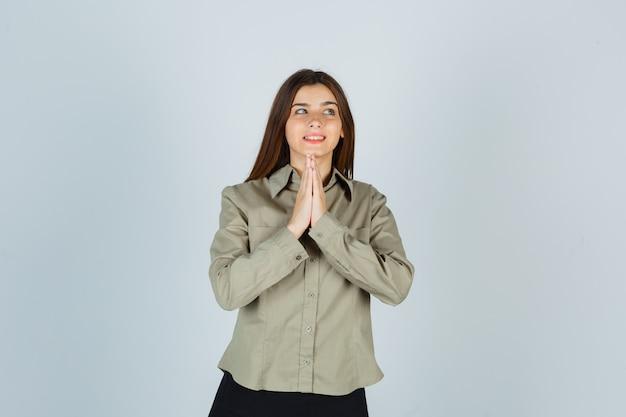 Retrato de jovem mulher mostrando gesto namastê na camisa