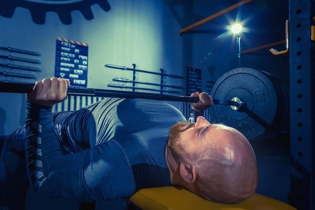 Retrato de jovem musculoso em forma super em forma, malhando na academia com barra