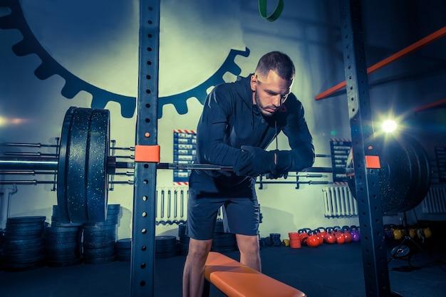 Retrato de jovem musculoso em forma super em forma, malhando na academia com uma barra no azul