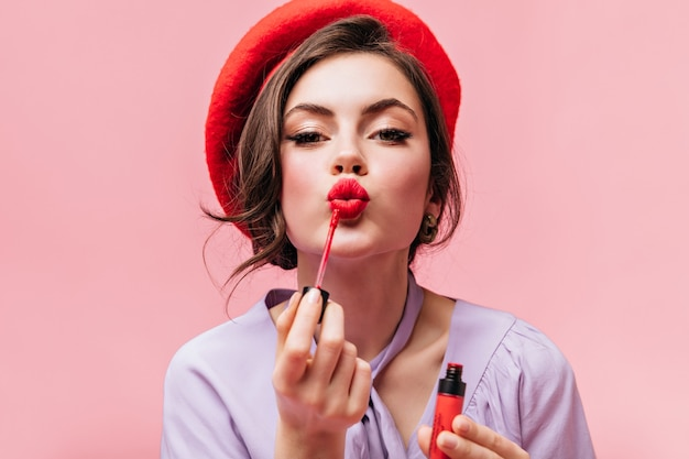 Retrato de jovem na boina vermelha pintando os lábios com batom brilhante no fundo rosa.