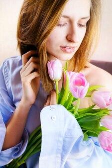 Retrato de jovem na cama segurando o buquê de tulipas cor de rosa. retrato romântico. .