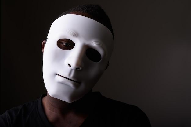 Retrato de jovem negro africano em um quarto escuro usando máscara