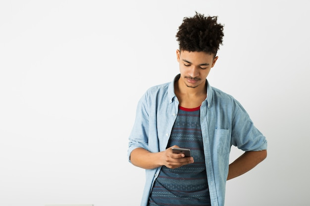 Retrato de jovem negro bonito, segurando um dispositivo digital, usando smartphone, isolado no fundo branco, juventude afro-americana, estilo hippie, estudante, ocupado