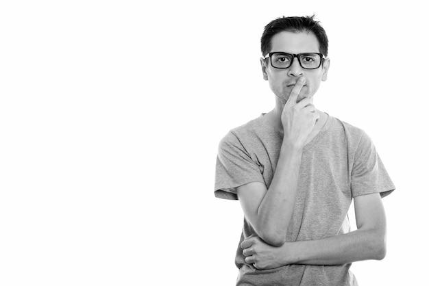 Retrato de jovem nerd magro usando óculos isolados no branco em preto e branco
