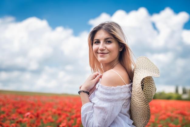 Retrato de jovem no campo de papoilas vermelhas