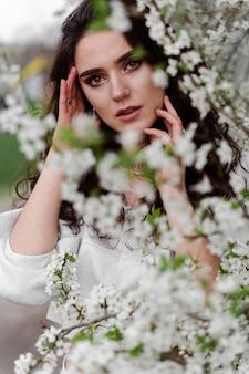 Retrato de jovem no jardim. garota atraente usava um vestido branco se passando perto de árvores florescendo.