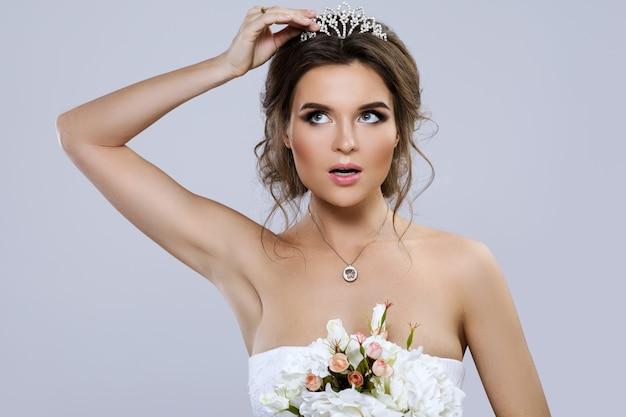Retrato de jovem noiva linda com buquê de flores