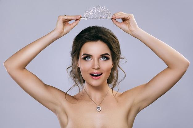 Retrato de jovem noiva linda segurando o diadema
