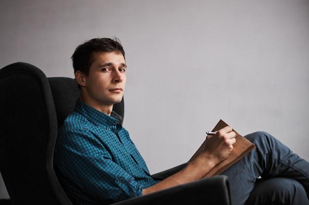 Retrato de jovem numa poltrona em frente à parede cinza