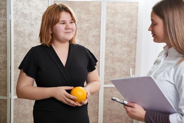 Retrato de jovem nutricionista sorridente no consultório. fazendo plano de dieta. mulher jovem visitando nutricionista em clínica de perda de peso
