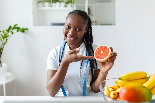 Retrato de jovem nutricionista sorridente no consultório. mesa de nutricionista com frutas saudáveis, suco e fita métrica. dietista trabalhando no plano de dieta.