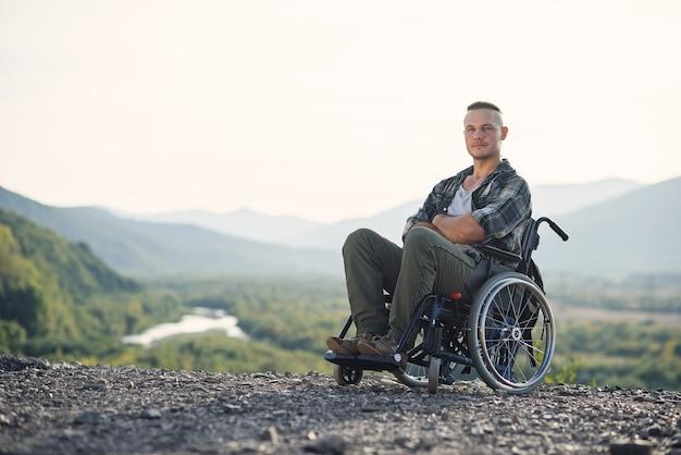 Retrato de jovem obstinado e motivado em uma cadeira de rodas apreciando a beleza da natureza