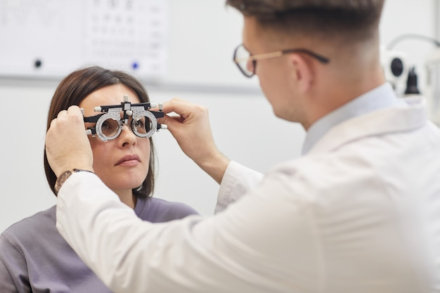 Retrato de jovem oftalmologista examinando paciente do sexo feminino