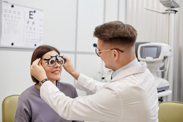 Retrato de jovem oftalmologista testando paciente do sexo feminino