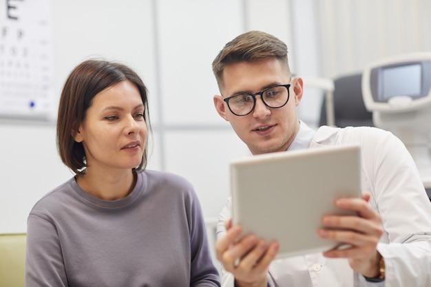 Retrato de jovem oftalmologista usando tablet digital enquanto consulta uma paciente
