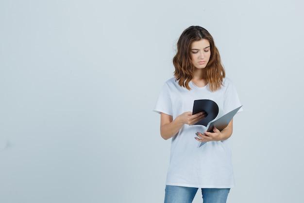 Retrato de jovem olhando as anotações na pasta em uma camiseta branca e olhando a vista frontal com foco