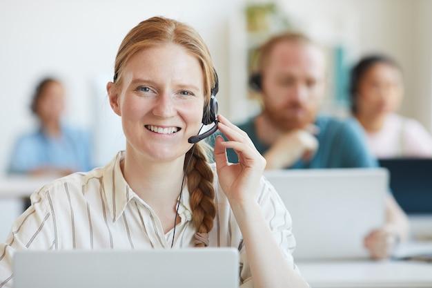 Retrato de jovem operadora com fone de ouvido sorrindo, ela, consultando clientes