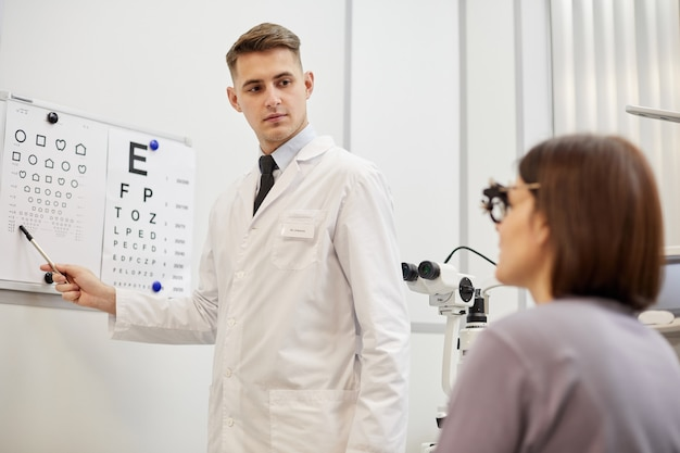 Retrato de jovem optometrista apontando para gráfico de visão