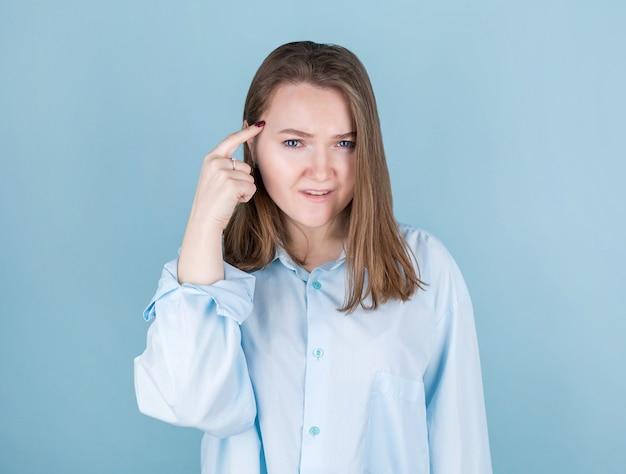 Retrato de jovem pensando com o dedo na cabeça isolado em azul