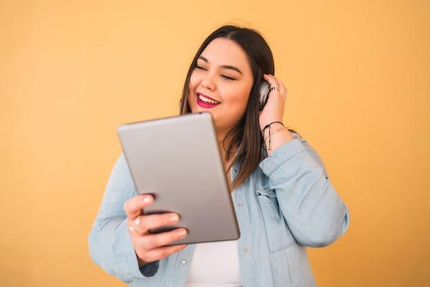 Retrato de jovem plus size mulher ouvindo música com fones de ouvido e tablet digital ao ar livre contra fundo amarelo.