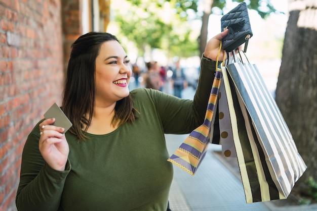 Retrato de jovem plus size mulher segurando um cartão de crédito e sacolas de compras ao ar livre na rua. conceito de compra e venda.