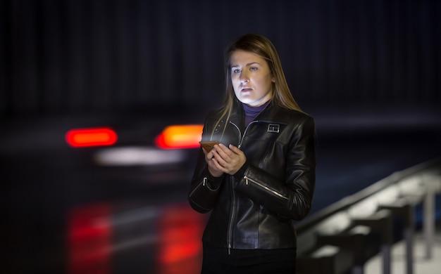 Retrato de jovem posando para a estrada à noite com o celular Foto Premium