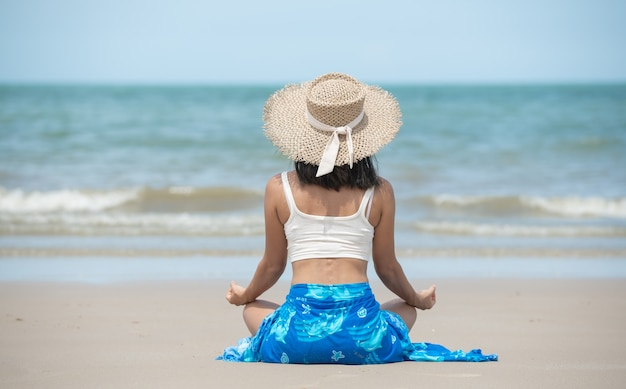 Retrato de jovem praticando ioga em ambiente de verão com chapéu e óculos de sol