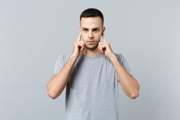 Retrato de jovem preocupado com roupas casuais, cobrindo as orelhas com os dedos
