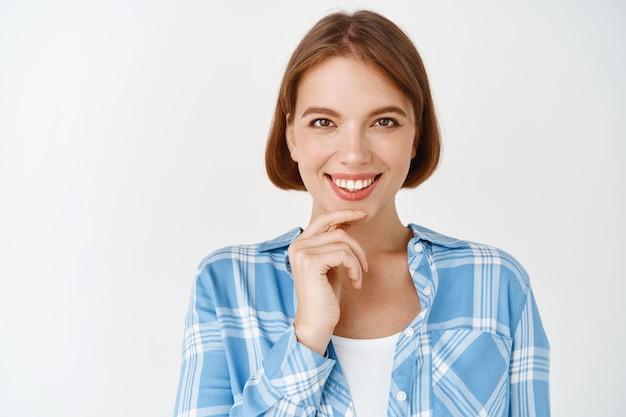 Retrato de jovem profissional com sorriso confiante, tocando o queixo e olhando, em pé na parede branca