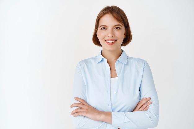 Retrato de jovem profissional confiante olhando determinado. mulher com blusa de escritório cruza os braços no peito, sorrindo motivada, em pé na parede branca