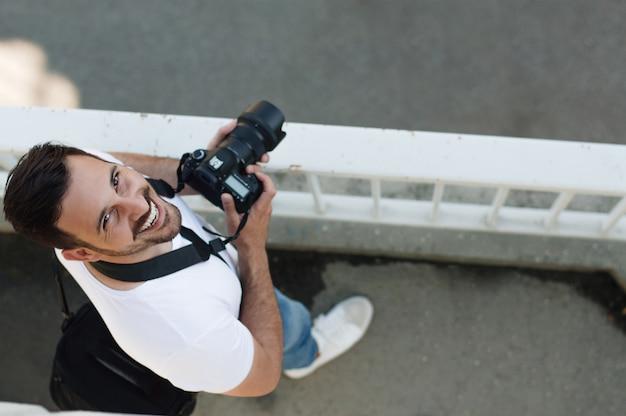 Retrato, de, jovem, profissional, homem, com, câmera, tiro, ao ar livre