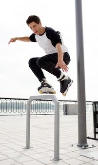 Retrato de jovem profissional pulando durante rolos patinando fora na rua