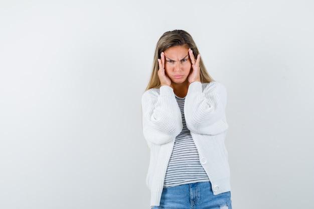 Retrato de jovem puxando a pele da testa com uma camiseta, jaqueta e uma vista frontal sombria