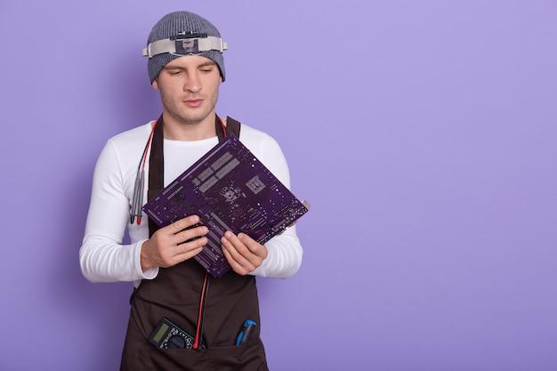 Retrato de jovem radiotricista experiente em pé isolado sobre lilás em estúdio, segurando a placa de circuito eletrônico