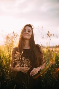Retrato de jovem rapariga bonita em um campo natural