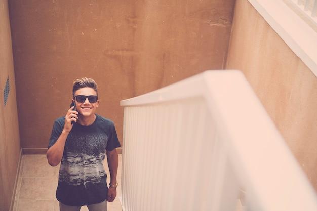 Retrato de jovem rapaz bonito alegre falando e ligando para o celular e sorrindo