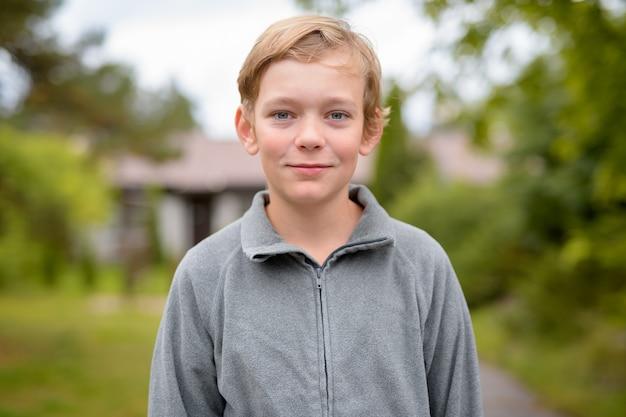 Retrato de jovem rapaz bonito com cabelo loiro em casa ao ar livre