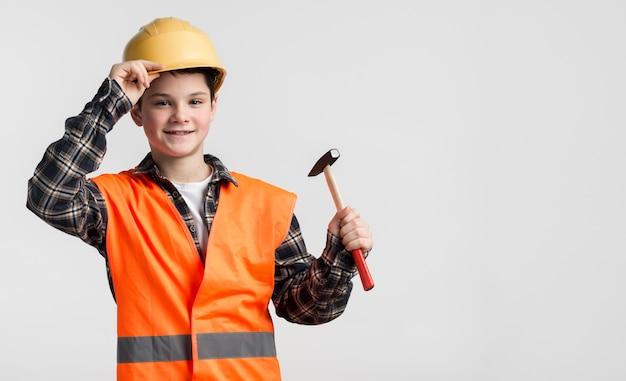 Retrato de jovem rapaz vestido como trabalhador da construção civil